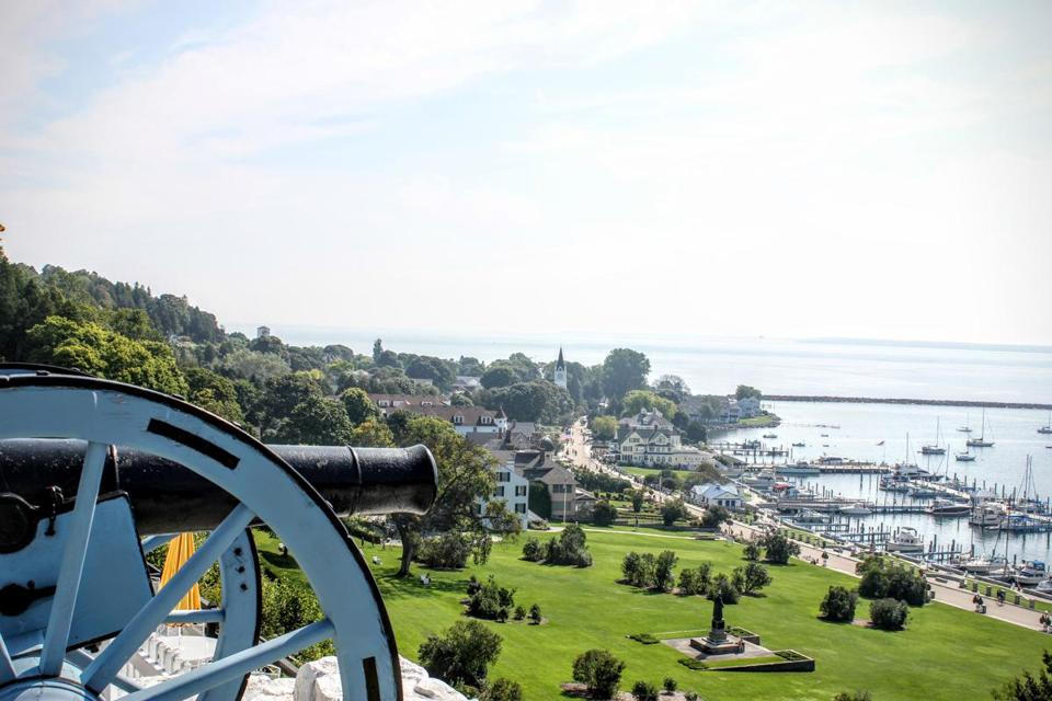 A cannon at Fort Mackinac, on Mackinac Island in Lake Huron, between  Michigan's two peninsulas. On an island that does not allow cars, horses, bicycles, and pedestrians crowd the streets in tourist season.